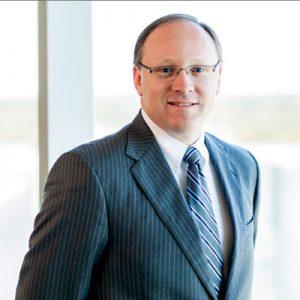 Lee Dixon wearing gray suit and tie