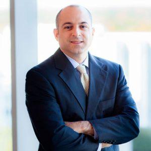 Luke Sbarra wearing dark suit and yellow tie