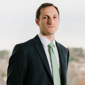 Charlie Vail wearing a dark suit and green tie