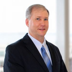 M. Duane Jones wearing a dark suit and blue tie