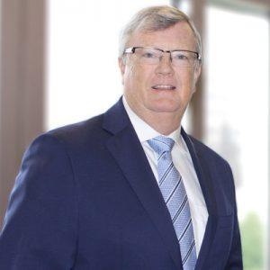 John Rabb wearing a navy blue suit and light blue tie