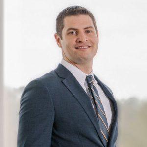Preston Rollero, wearing gray suit and tie