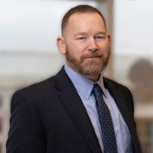 Matthew Lancaster, wearing a dark suit and tie