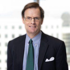 Allen Smith wearing a dark suit and striped green tie