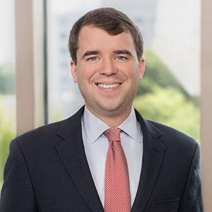 Paul Allen, Jr. wearing a dark suit and red tie